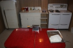 Working in the vintage kitchen -Admiral Fridge and Stove, along with a classic red table and the pasta machine.