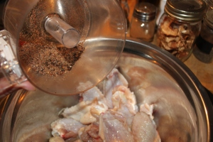 Dry mix being sprinkled on chicken wings that have been drizzled with olive oil