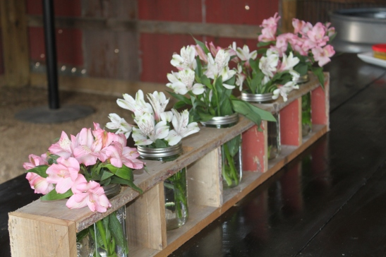 Flowers fill the mason jars on the barn table