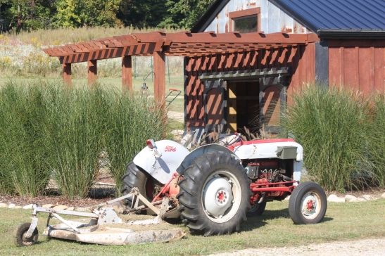 The old ford tractor rests up by the barn pergola  after a long day of mowing