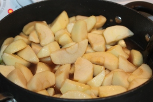 Apples folded into syrup mixture and being heated.