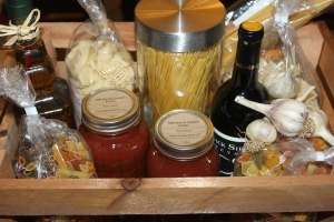 Home-made pasta crate. Filled with our pasta sauce, garlic, crushed red pepper flakes and pasta and a bottle of wine. Hopefully, someday soon the wine can be from our farm too!