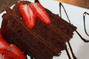 Triple layer chocolate cake with a few sweet strawberries makes a delicious Valentine's day treat.