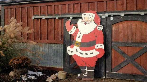 Santa posing for a picture in front of the barn