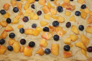 Add batter, diced peaches, and blueberries to complete the first layer of the cake